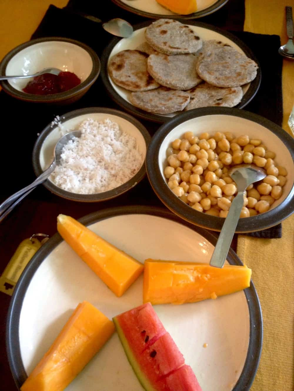 Breakfast - Strawberry jam, coconut flakes, chickpeas, fruits and pancakes.