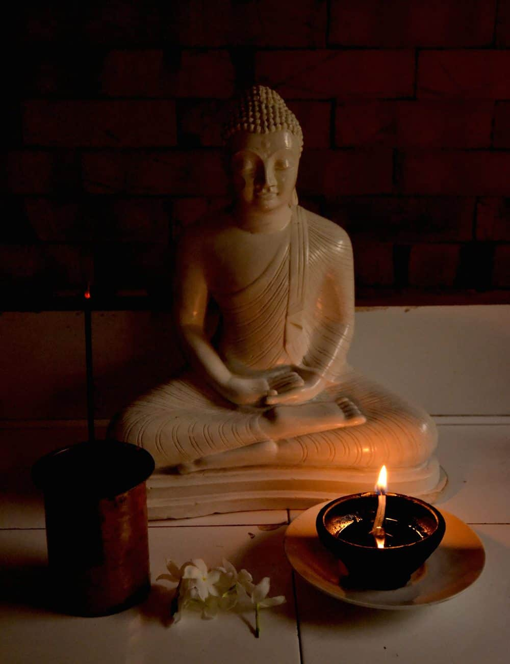 Buddha statue with a candle.