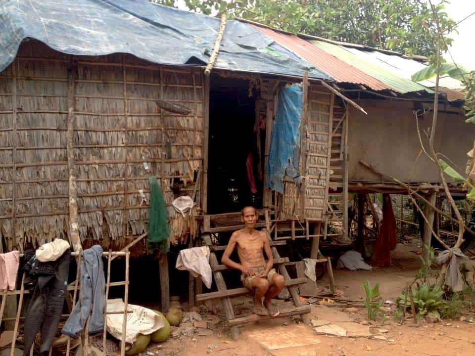 A man is sitting outside his hut