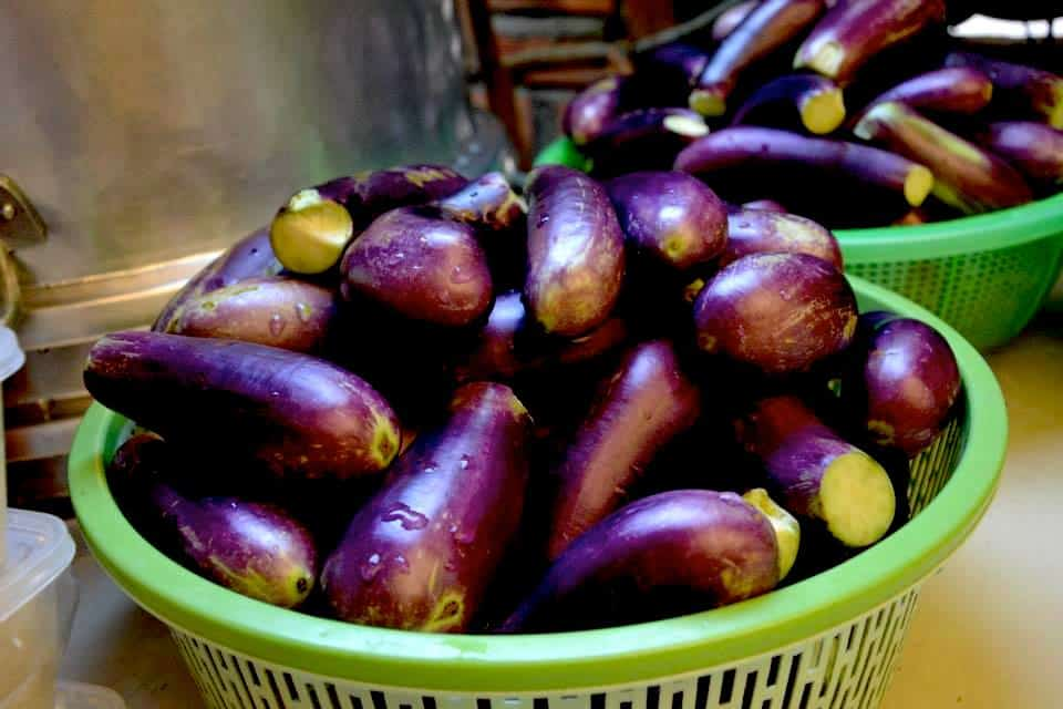 Fresh eggplants in green bowls