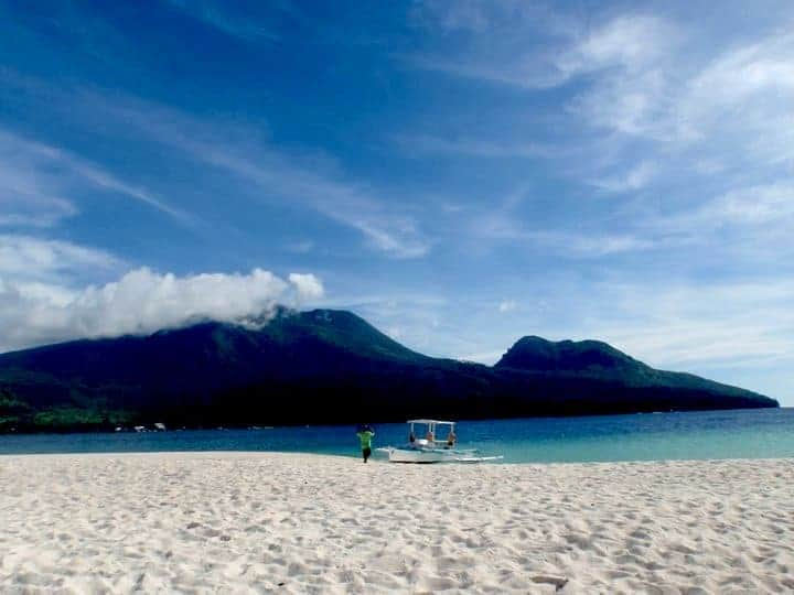 White island in Camiguin with a man with a boat.