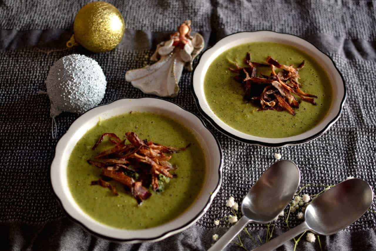 Vegan Broccoli soup in white plates and Christmas decoration