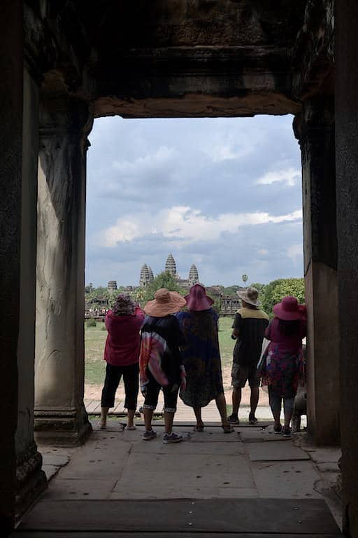 Tourists with hats in a angkor wat temple.