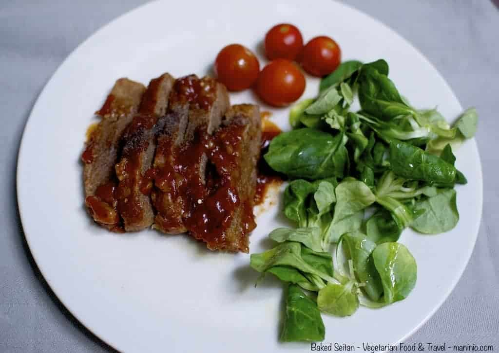 Seitan with green salad and cherry tomatoes in a white plate
