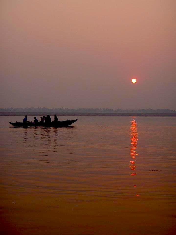 Sunrise and a boat with men in Ganges river