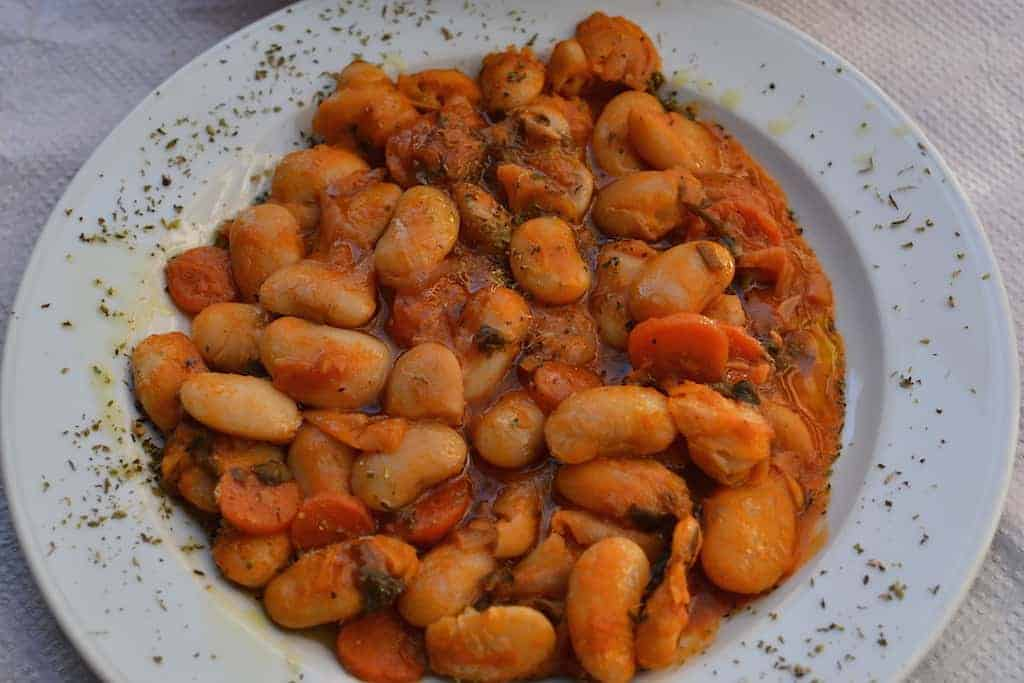 Beans with tomato in a white plate with oregano