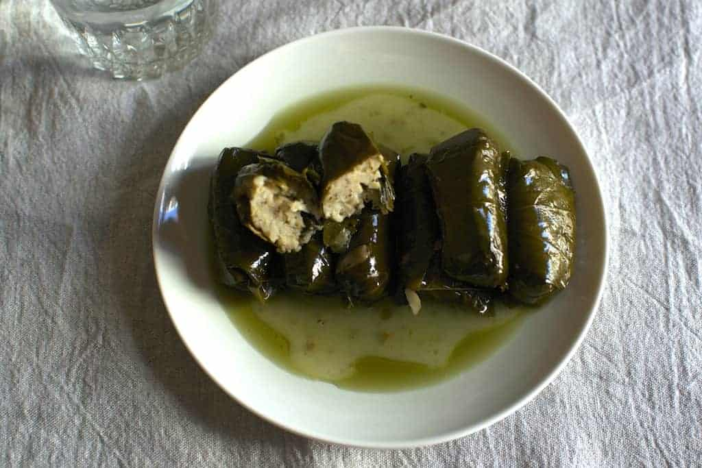 Stuffed Dolmadakia with olive oil in a white plate