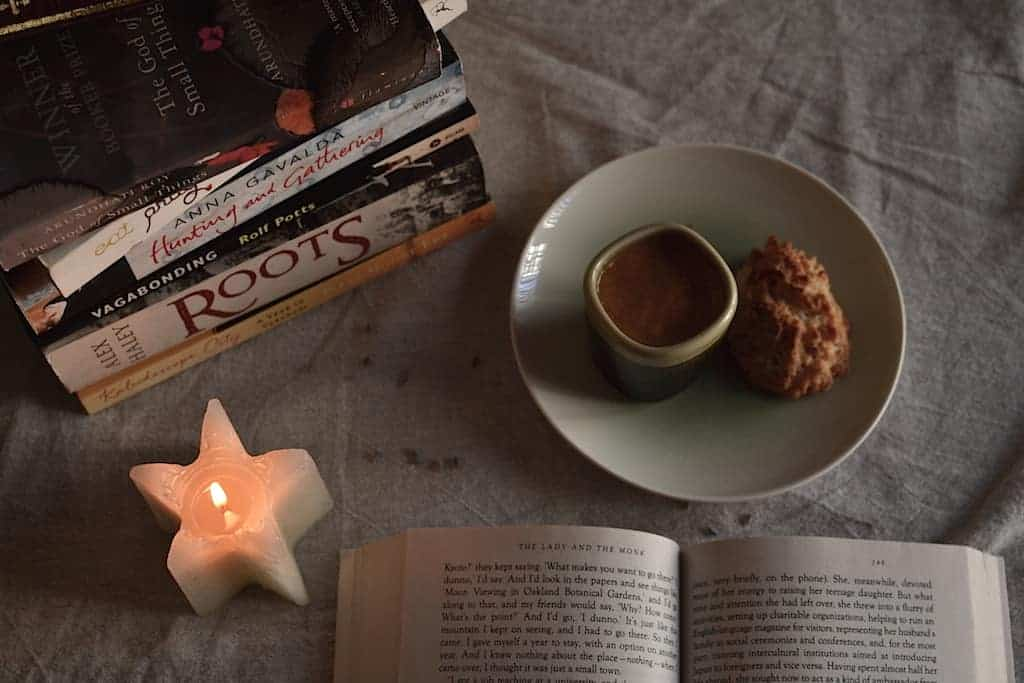 Wanderlust books, coffee, cookie and a candle.