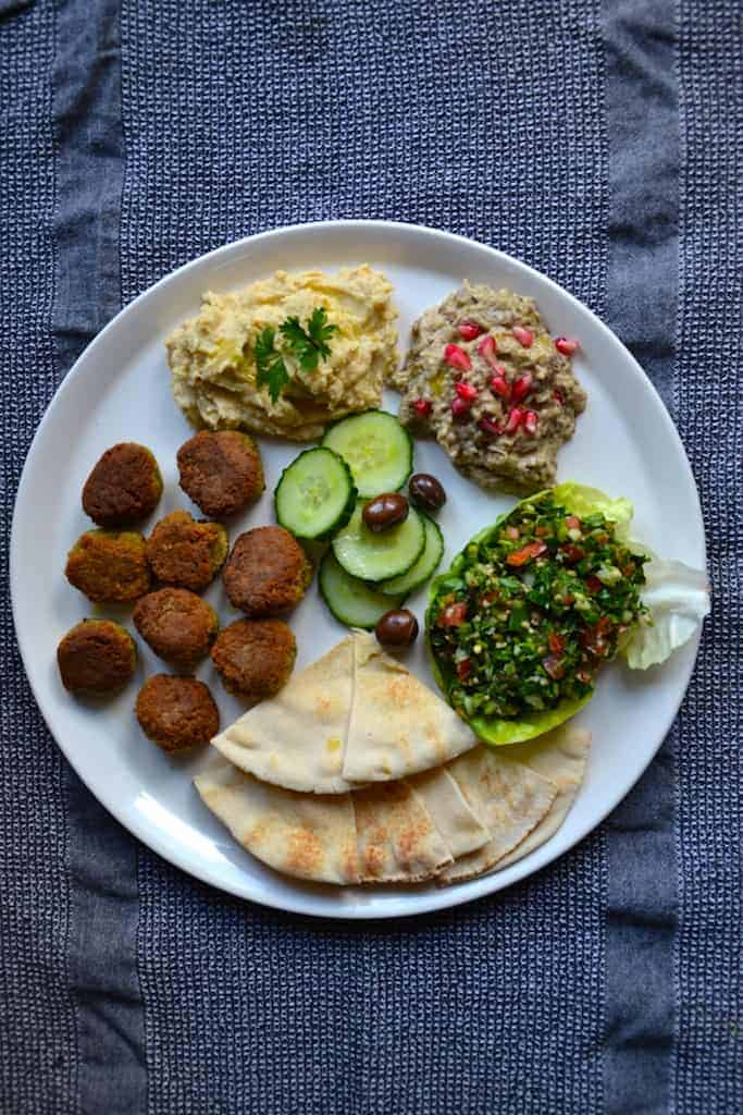 Arabic plate with tabouleh, hummus, falafel, olives, slices of cucumber and babaghanoush