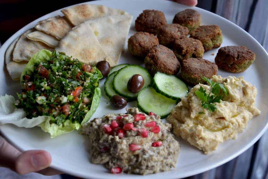 Mutabal, Falafel, olives, pitta bread, hummus and slices of cucumber in a white plate
