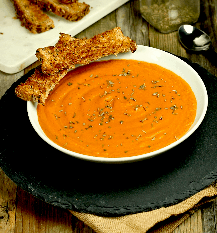 A white bowl with carrot soup and pieces of bread.