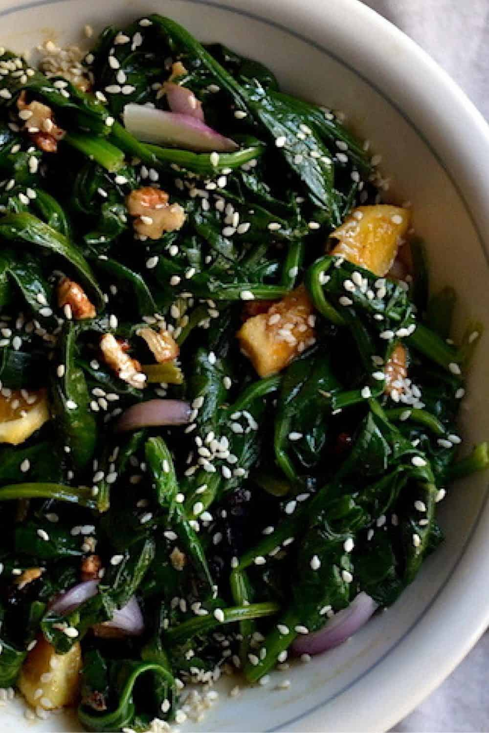 Salad with Spinach and Orange in a white bowl. - Vegan Easter Recipes