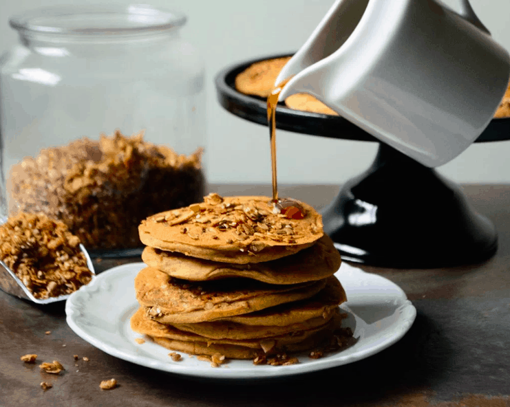 Granola ackee Pancakes with a jar of agave syrup