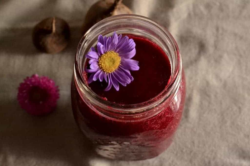 Beetroot Smoothie with a purple flower decoration