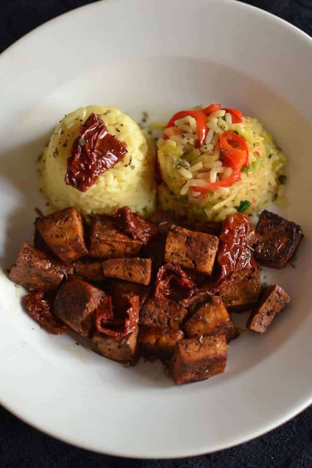 Baked tofu with vegetable rice in a white plate - - Vegan Easter Recipes