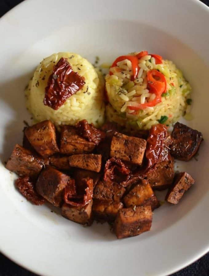 Baked tofu with vegetable rice in a white plate