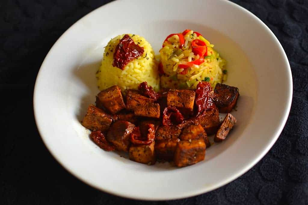 Crispy Baked Tofu with Two Scoops of Vegetable Rice in a White Dish