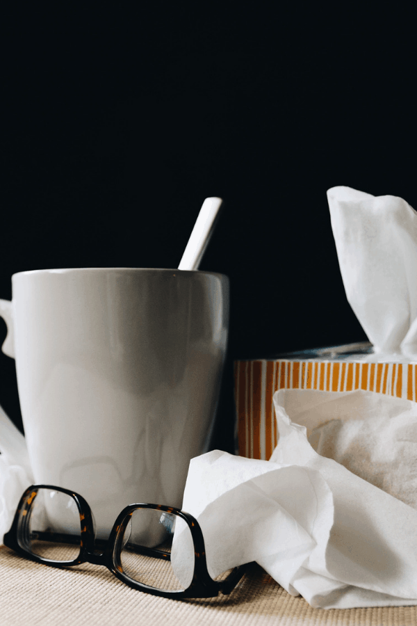 a cup with tea, tissues and blsck glasses, allergic rhinitis