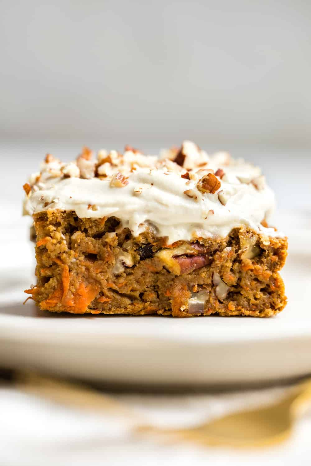 A sliece of vegan carrot cake with white frosting