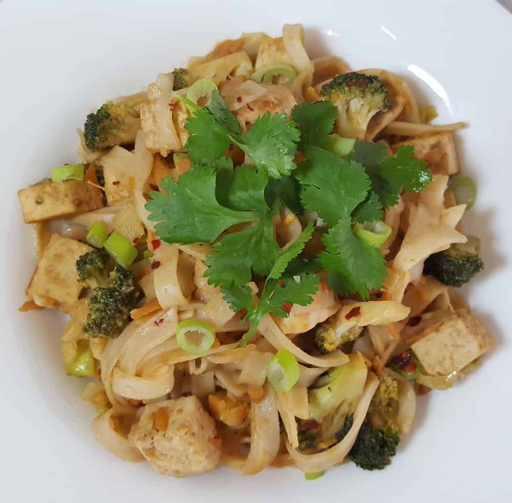Vegan pad thai with basil served in a white plate - - Vegan Easter Recipes