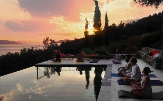 Yoga beside the pool during sunset