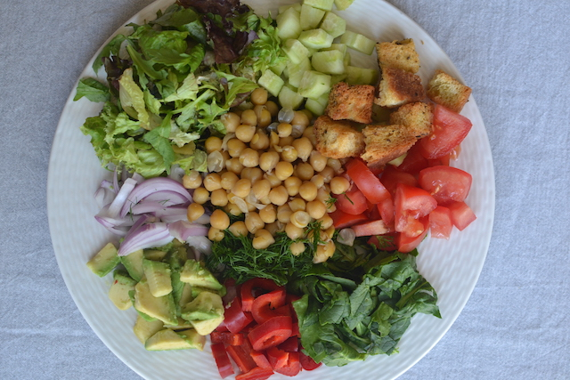 chcikpeas, lettuce, tomatoes, greens in a white plate