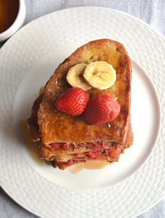 vegan french toast with strawberries and bananas in a white plate