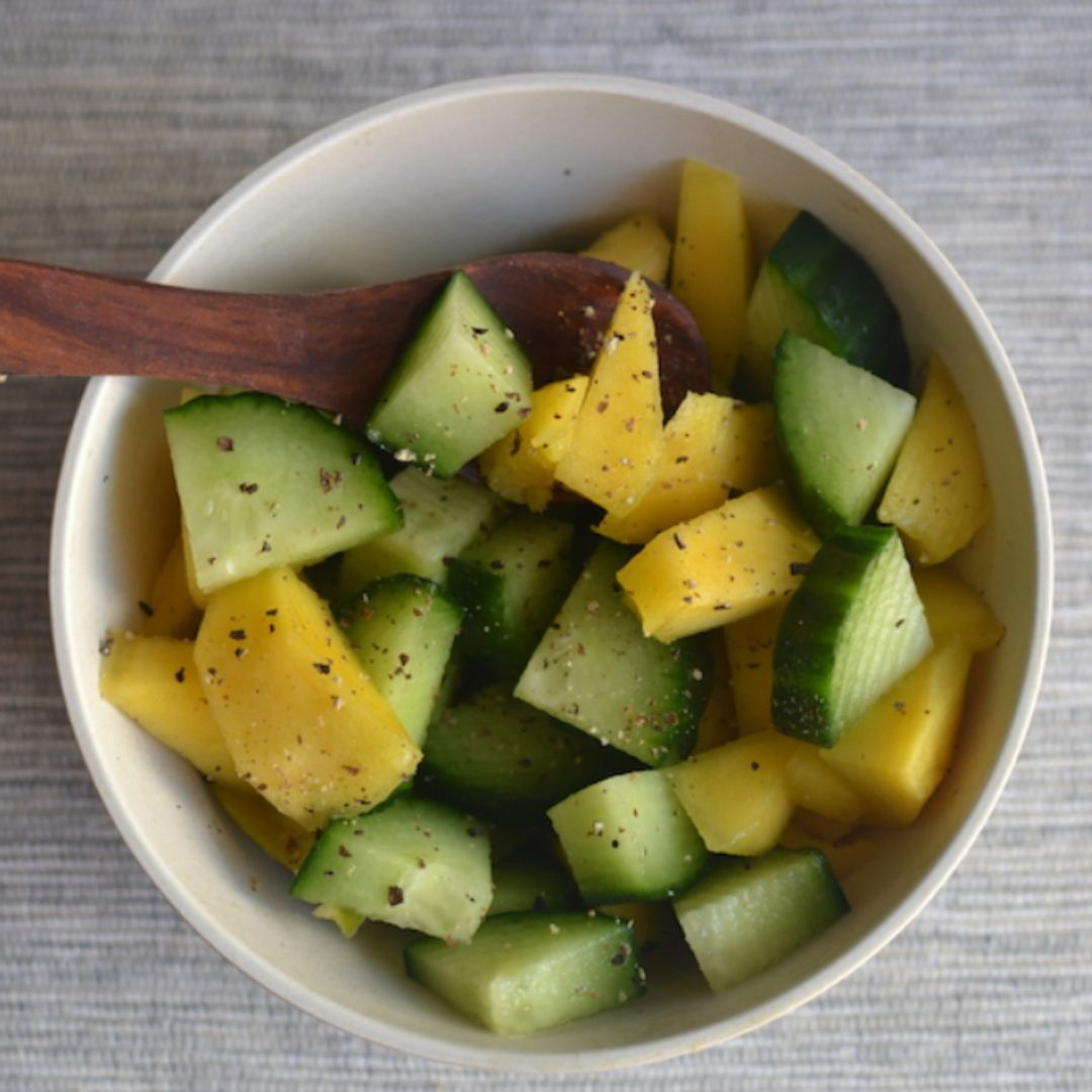 cucumber and mango salad in a white bowl with a wooden spoon