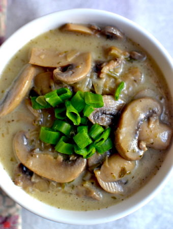 a plate of mushroom soup with chives