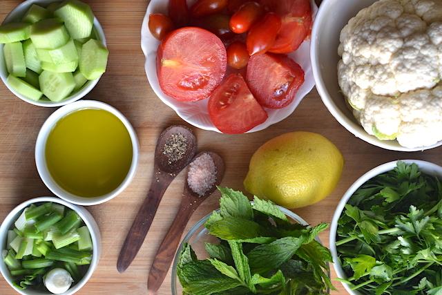 cauliflower, parsley, dill, olive oil, pepper, salt, onions, cucumbers, lemon in wooden board