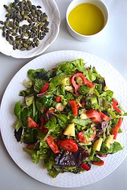 salad in white plate, sunfloer seeds and olive oil in white jar
