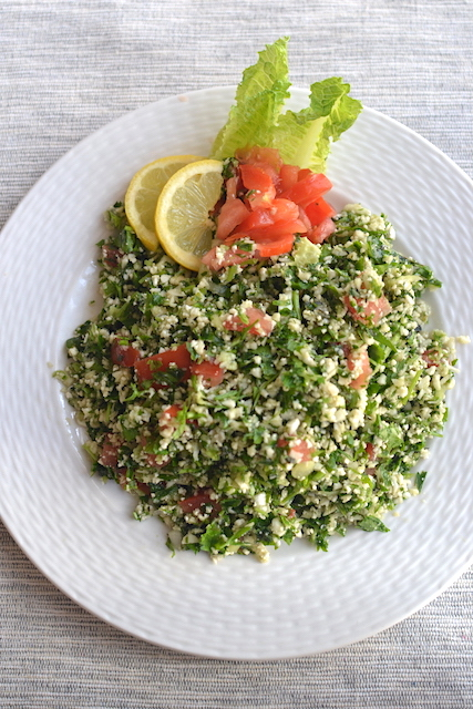 Cauliflower tabbouleh in a white plate with lettuce lemon and tomatoes