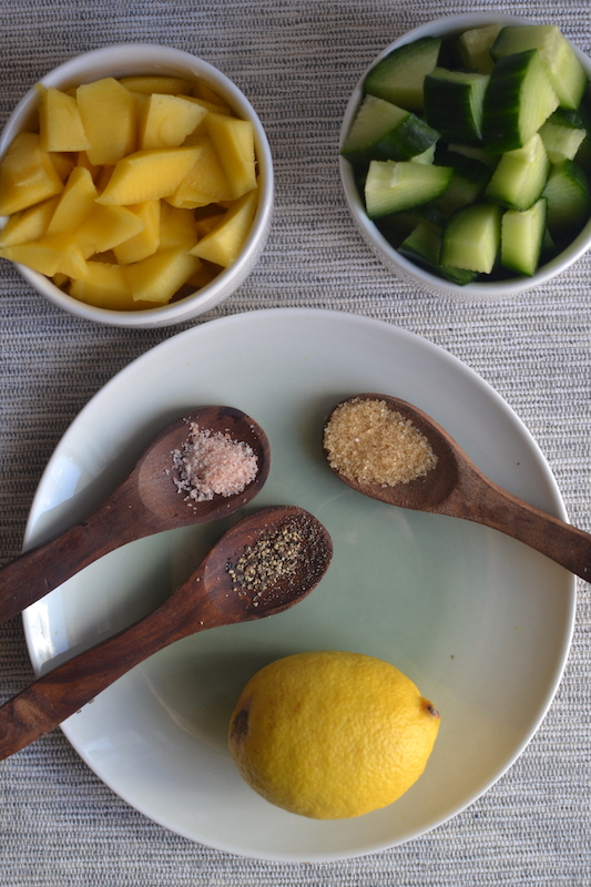 mango, cumber, lemon, oregano and pepper in wooden spoons and white plates