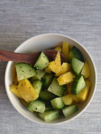 ccumber avocado sala in a white bowl with a wooden spoon.