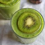 kiwi smoothie with a kiwi slice on the top of a glass