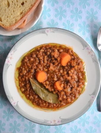 lentil soup in white plate in a blue cloth table