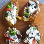 baked potatoes with veggies and cream in a wooden palte