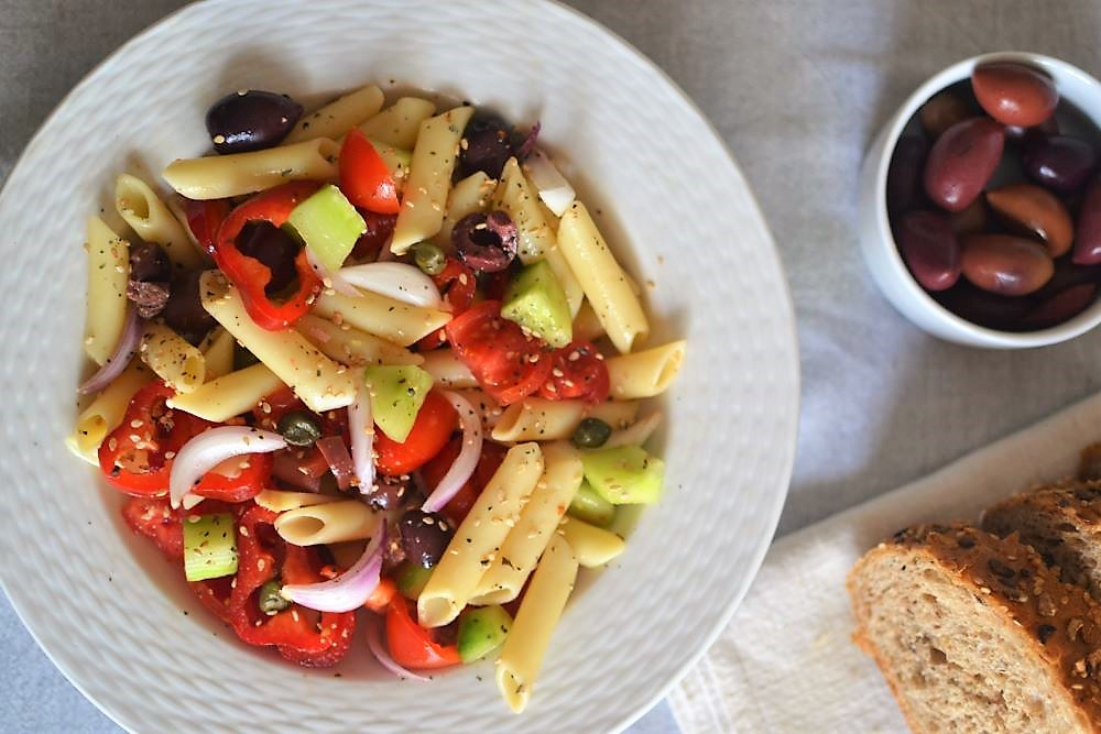 pasta salad in a white plate with olivew and bread