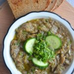 EGGPLANT DIP in a white plate with baked bread