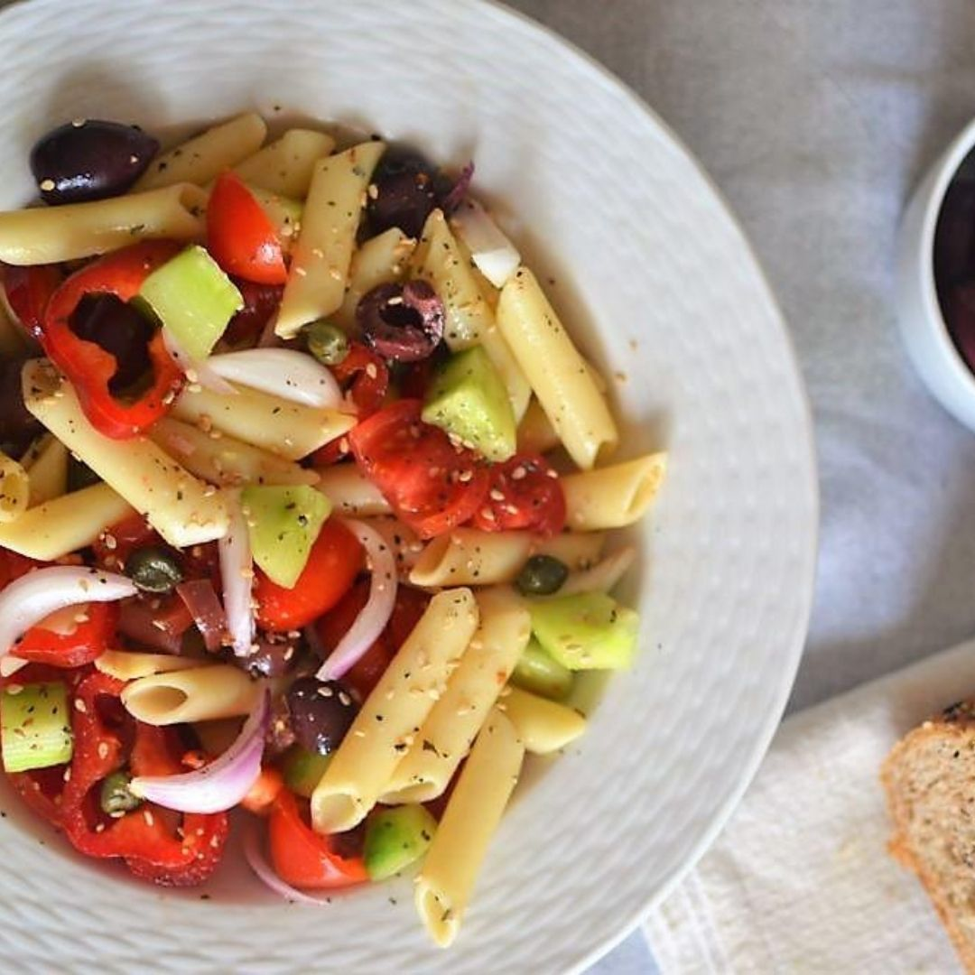 Pasta salad with tomatoes, olives, cucumber and onions