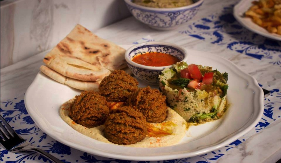 4 falafels with hummus and red sauce in a white plate